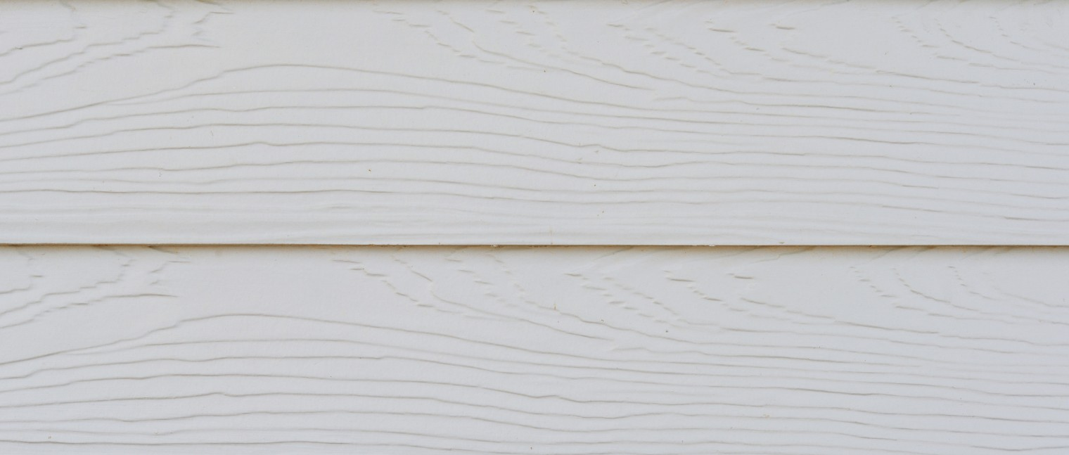 An up close photo of fiber cement siding on the side of a house.