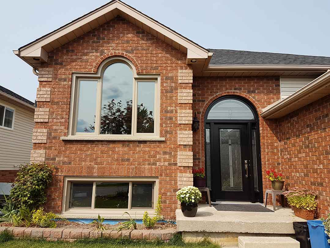The front face of a house with casement, fixed and custom shaped windows installed.