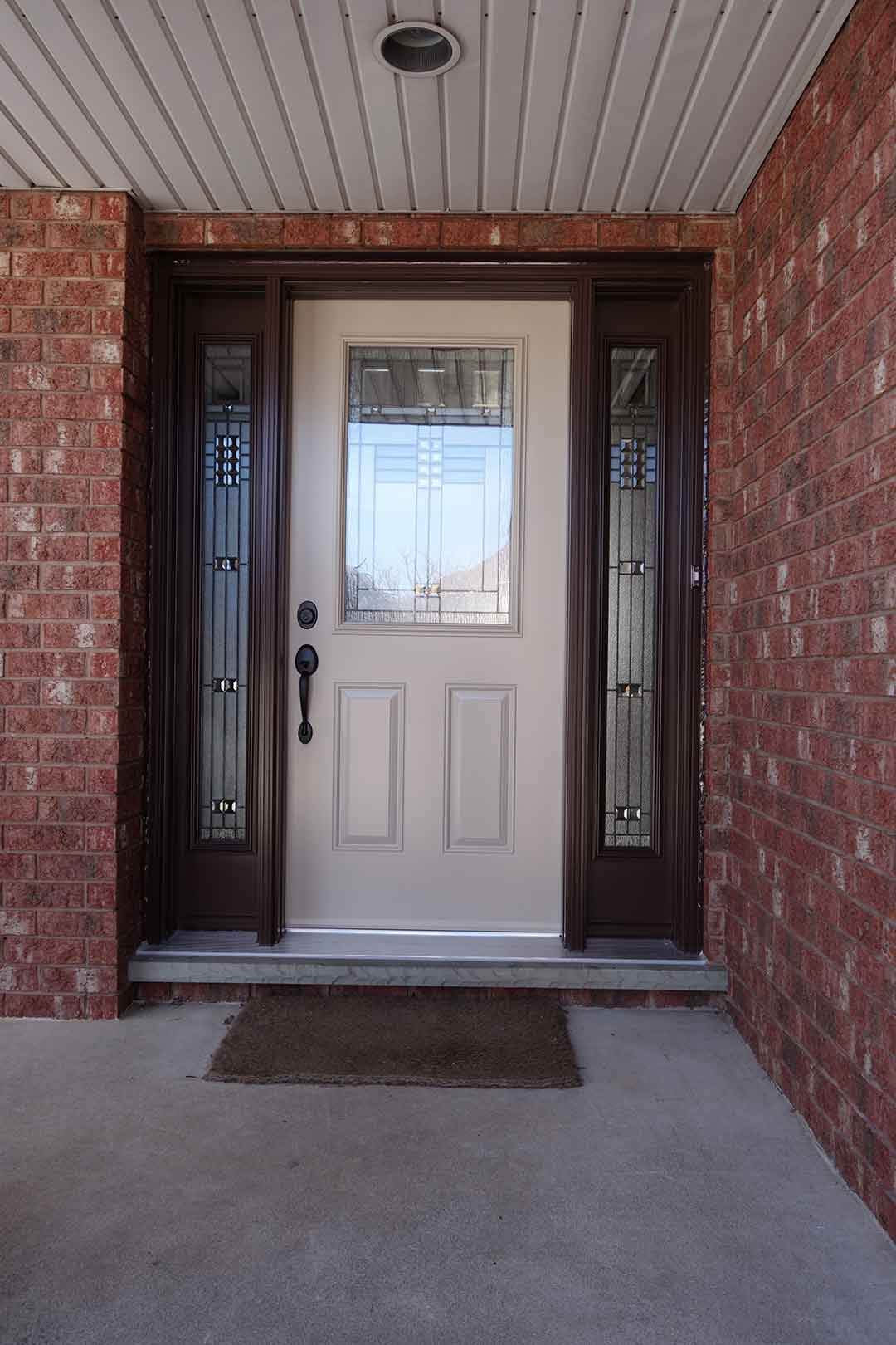 A beige front entry door with a stained glass insert and sidelites