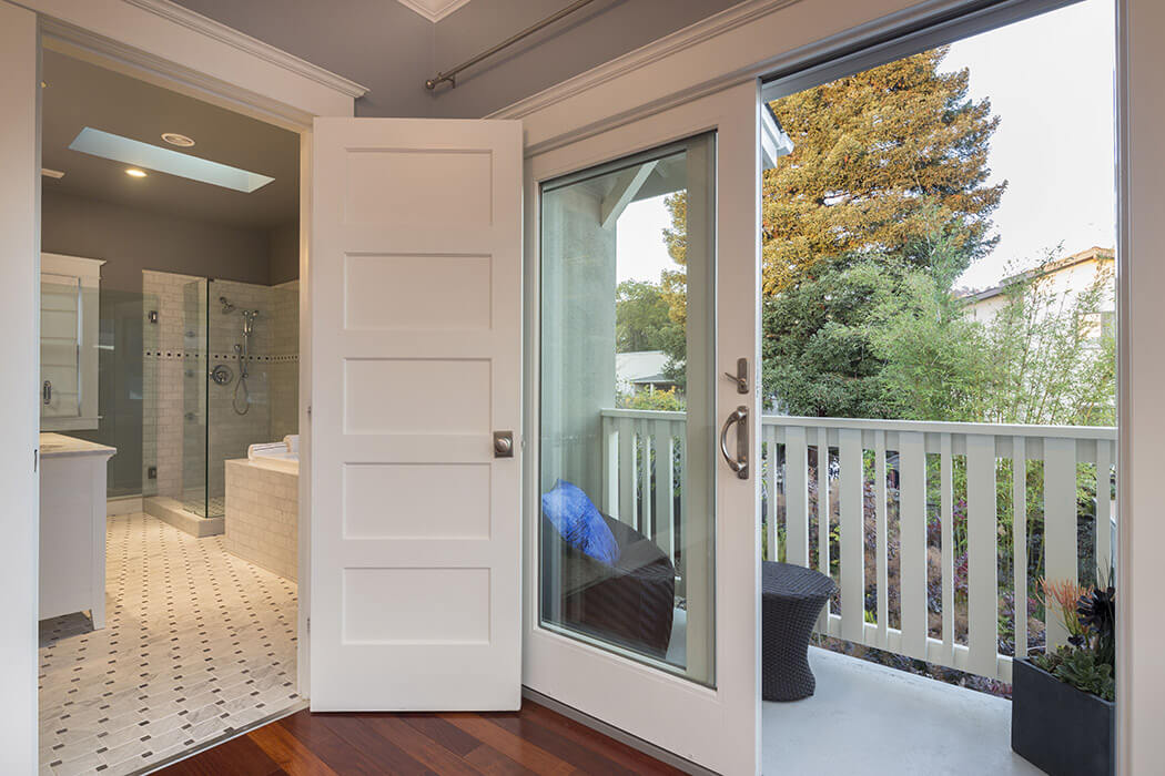 White, sliding patio doors looking out onto a park view.