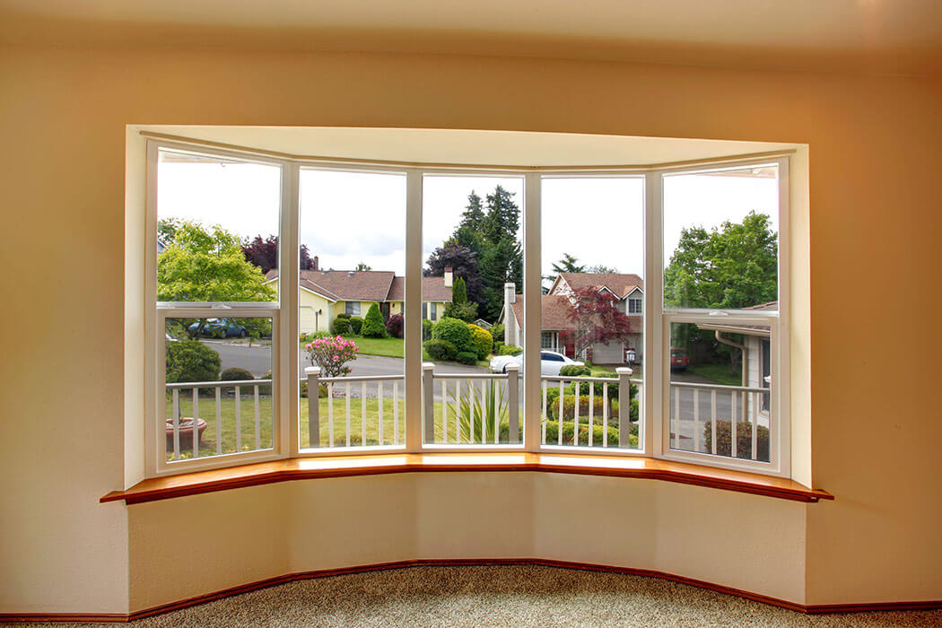 Large five panel replacement bay window with two double hung windows.