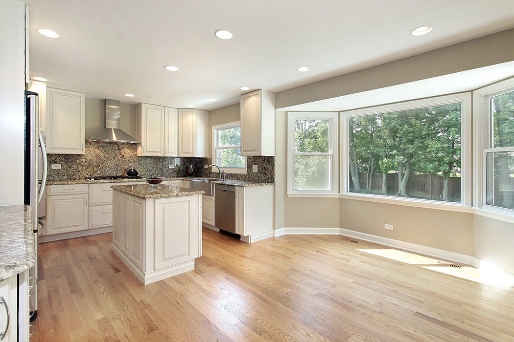 Refinished kitchen with large replacement bay window and granite countertops.