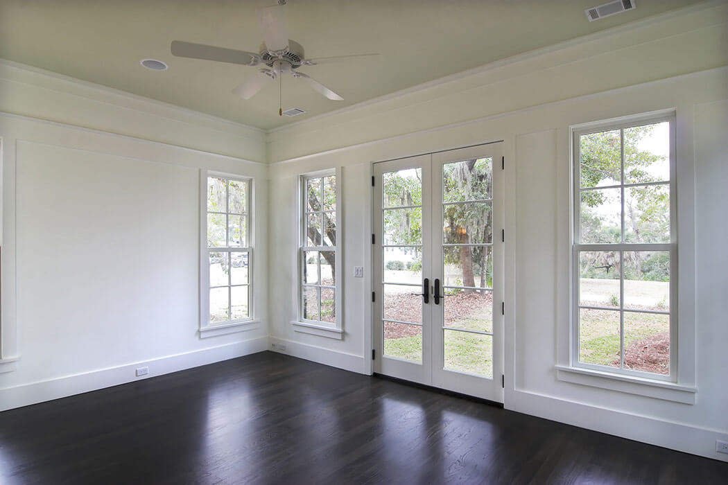 An empty lving room with three double-hung windows and large french doors leading to the backyard.