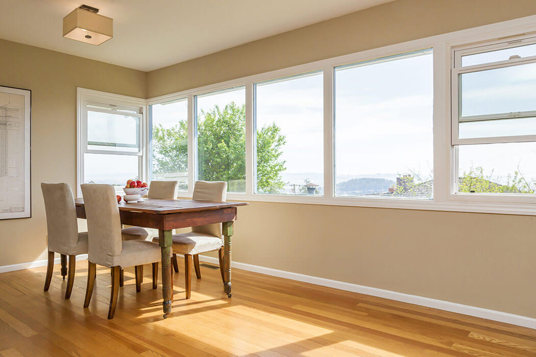 Dining room with four large picture windows and two replacement double hung windows over a modern table.