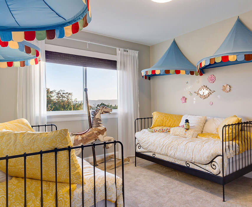 Kid's bedroom with clown-themed sheets and double sliding window in background.
