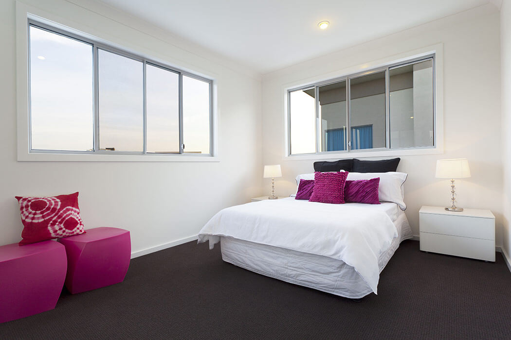 Modern bedroom with fuscia accent coloring and two pvc double sliding windows.