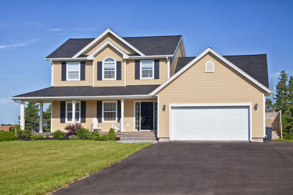 Eco-friendly vinyl siding which is almond coloured on a large suburban home.