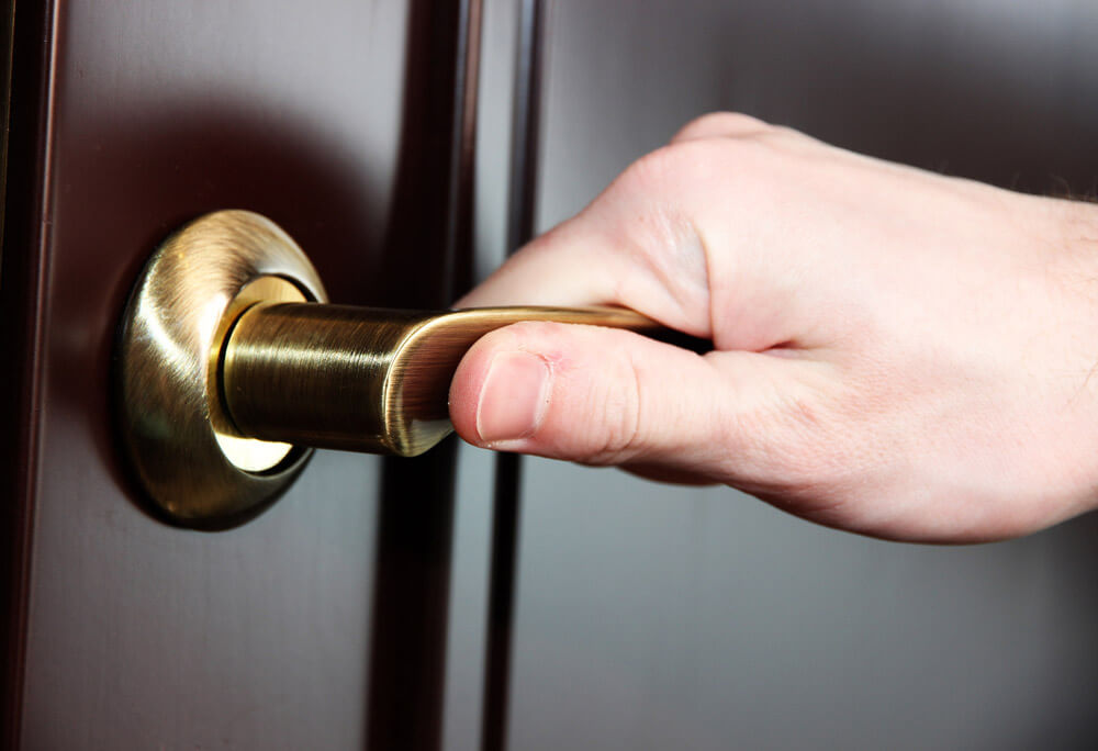 A close-up view of a hand opening a brass storm door handle.
