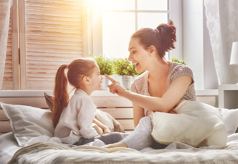 A mother and daughter play on a bed while the sun beams through the bedroom window.