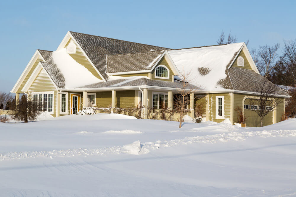 A large home in a winter setting with beige siding and accent storm door.